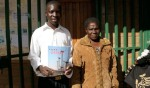 "Kamkwamba standing with the librarian who found the book ""Using Energy,"" which he used to make a windmill."